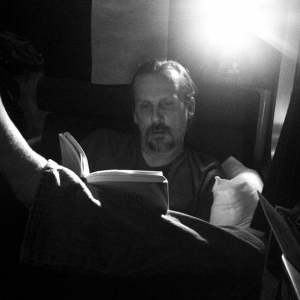 Jim reading on a train